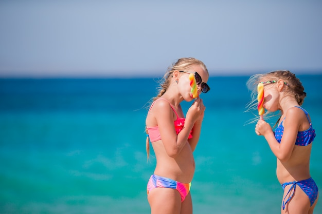 Happy little girls eating ice-cream during beach vacation. people, children, friends and friendship concept