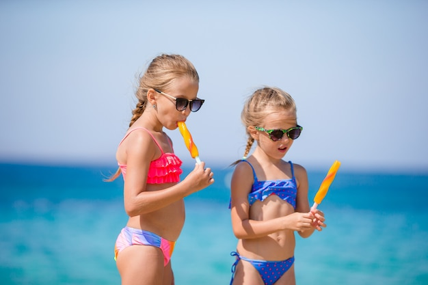 Happy little girls eating ice cream during beach vacation