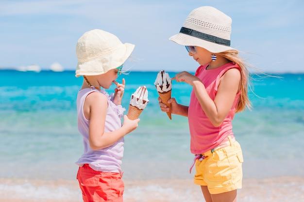해변 휴가 동안 아이스크림을 먹는 행복 소녀.