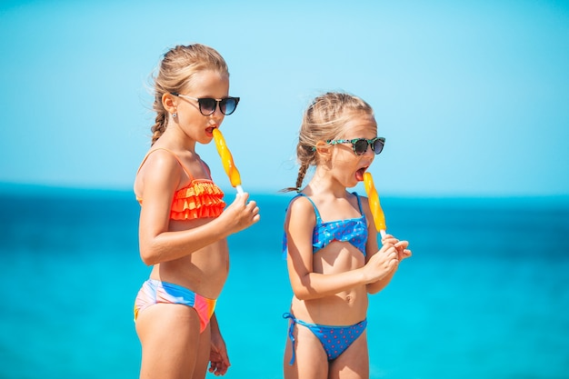 Happy little girls eating icecream during beach vacation people children friends and friendship concept