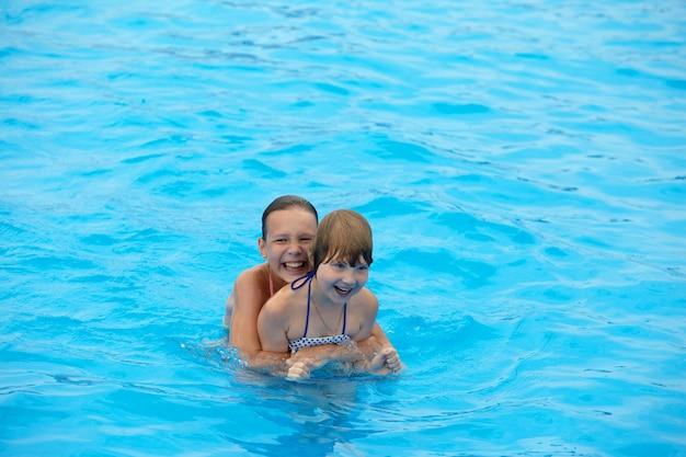 幸せな小さな女の子はプールで泳ぐのを楽しんでいます