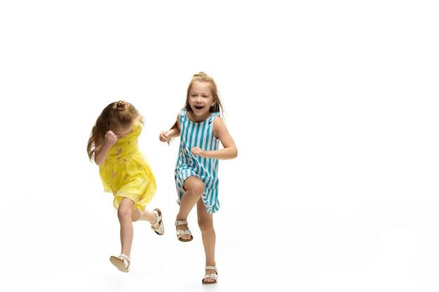 어린 시절 흰색 배경에서 점프하고 달리는 행복한 어린 소녀들