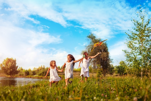 Happy little girls running with kite in summer park with mother, children having fun playing