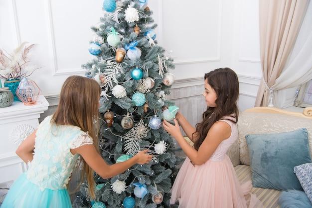 행복한 어린 소녀 자매들은 겨울 휴가를 축하합니다. 크리스마스 트리를 장식합니다. 새해 복 많이 받으세요. 크리스마스 때. 크리스마스 선물을 가진 귀여운 어린 소녀. 배달 크리스마스 선물.