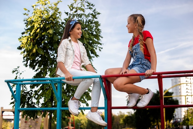 Happy little girls talking on the playground