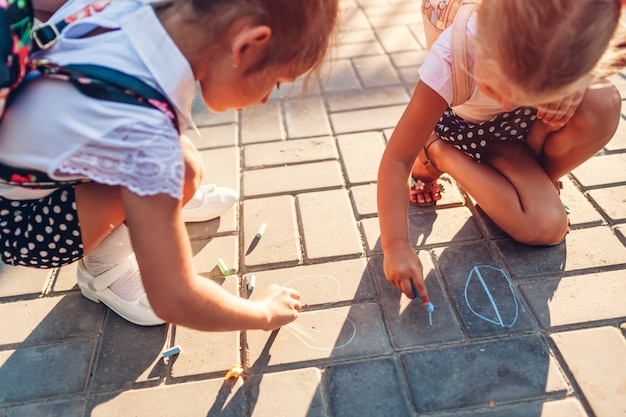 Happy little girls wearing backpacks and drawing with chalk outdoors primary school.