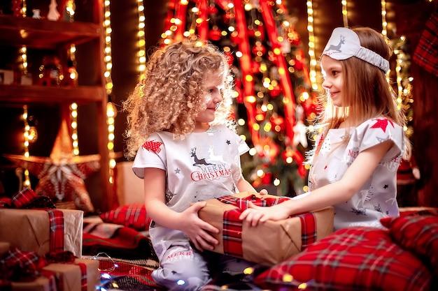 Счастливые маленькие девочки в рождественской пижаме открывают подарочную коробку у камина в уютной темной гостиной в канун рождества.
