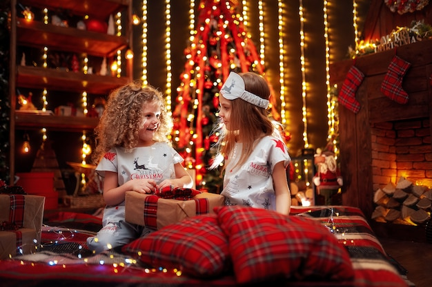 Happy little girls wearing christmas pajamas open gift box by a fireplace in a cozy dark living room on christmas eve.