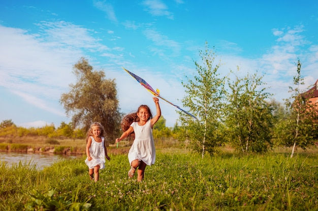 Happy little girls with kite running on meadow in summer park, children having fun playing
