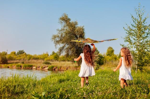 草原で実行されている凧で幸せな女の子。屋外で遊ぶ子供たち