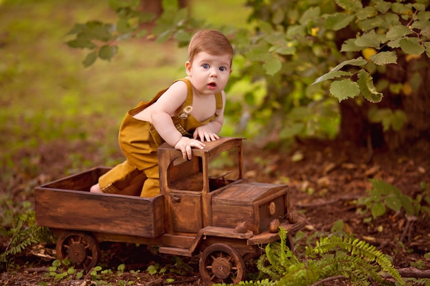 Счастливый маленький мальчик 8-12 месяцев сидит в деревянной детской машине на природе.