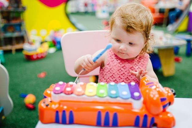 Счастливый маленький ребенок, девочка 1-2 лет играет на музыкальном инструменте ксилофон в игровом центре, развлечение детской комнаты на день рождения. развлечения в помещении. Premium Фотографии