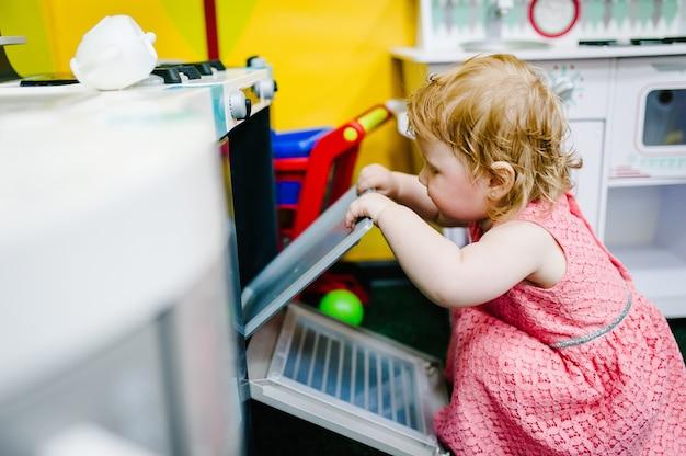 행복한 어린 아이, 1년 된 여자아이, 어린이 방, 유치원 또는 집에서 장난감 부엌을 가지고 노는 것. 게임 센터. 어린이집에서 플라스틱 식기를 가지고 노는 아이.