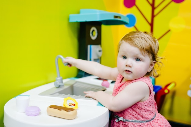 Happy little kid, baby girl one year, playing with a toy kitchen in children room, kindergarten or home. game center. child playing with plastic tableware, wash basin at daycare.