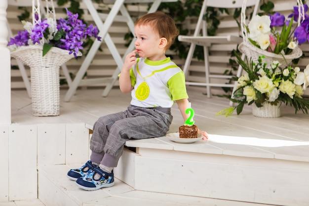 그의 생일을 축하하는 행복한 어린 소년은 실내에서 케이크 한 조각을 들고 있습니다. 아이들을 위한 생일 파티. 평온한 어린 시절, 행복. 두 살.