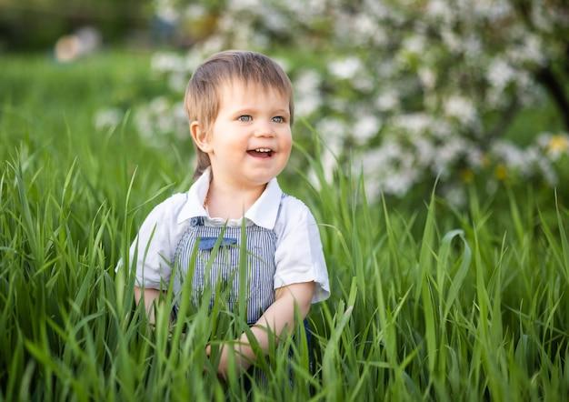 아름 다운 파란 눈을 가진 유행 파란색 점프 수트에 행복 한 작은 아이. 사과 나무를 배경으로 녹음이 가득한 꽃이 만발한 공원의 키 큰 푸른 잔디에서 재미있는 놀이를 합니다.
