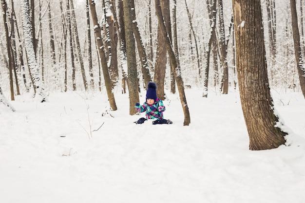 Счастливый маленький ребенок играет в снегу, хорошая зимняя погода.