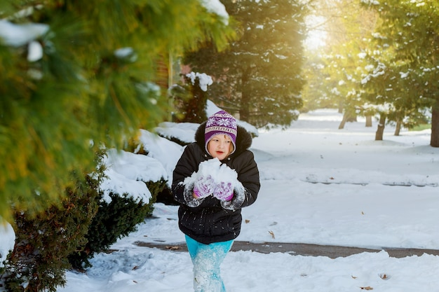 Happy little kid is playing in snow, good winter weather
