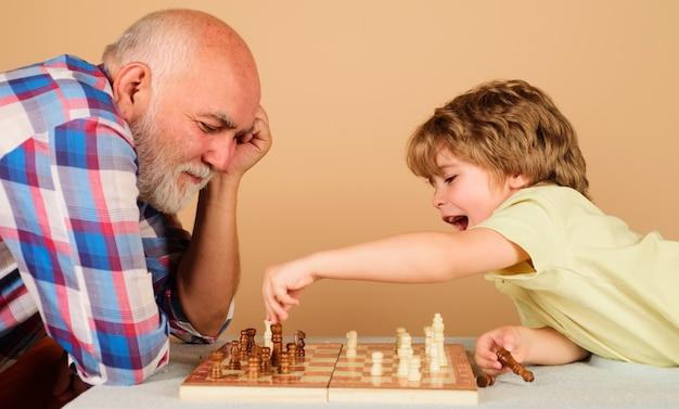 おじいちゃんとチェスをしている幸せな小さな子供。祖父と孫との家族関係。ボードゲームをしているおじいちゃんと孫。