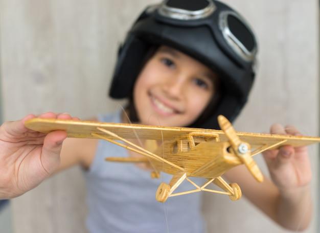 木製の飛行機で遊んでいる幸せな小さな子供