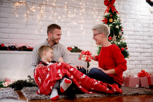 Happy little kid sitting on a carpet while holding a red blanket and getting a gift from his careful beautiful parents for christmas holidays at home.