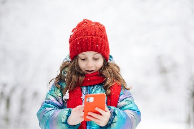 Счастливый маленький ребенок использует смартфон с забавным приложением маски для лица, глядя на экран сотового телефона, улыбается на что-то смешное.