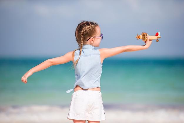 白い砂浜で手におもちゃの飛行機で幸せな子供