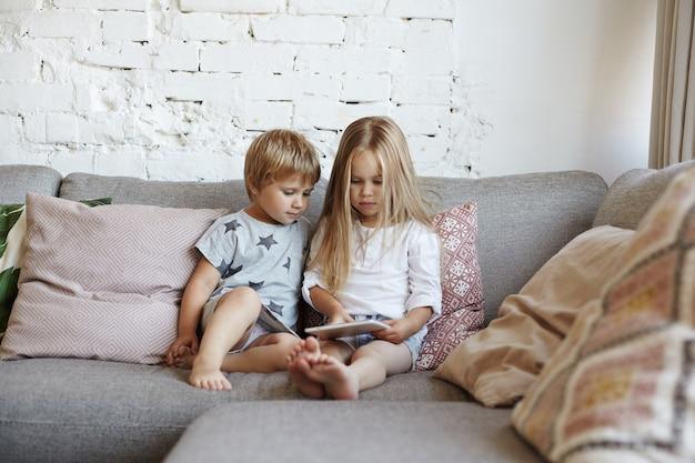 幸せな小さな子供たちはリビングルームに座っています