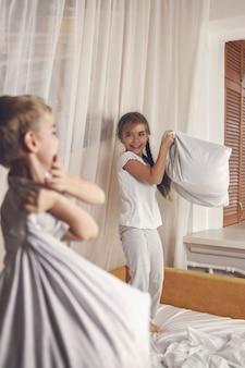 Счастливые маленькие дети в пижамах устроили драку подушками в постели в спальне