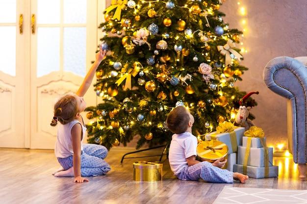 Happy little kids in pajamas looking at christmas tree in beautiful living room