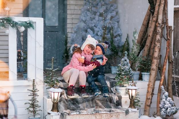 クリスマスの装飾が施された家のポーチに座って、屋外で雪が降る幸せな小さな子供たち