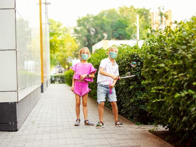 Счастливые маленькие дети в защитной маске прыгают и бегают по городской улице. выглядит счастливым, жизнерадостным, искренним. copyspace. детство, концепция пандемии. здравоохранение, пандемия коронавируса.
