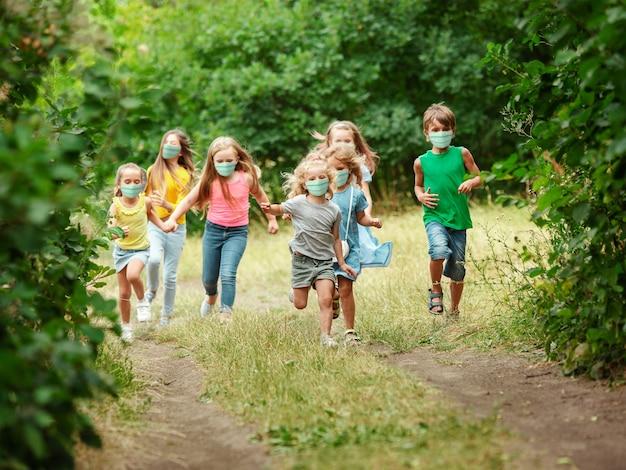 Счастливые маленькие дети в защитной маске прыгают и бегают по лугу, лесу. выглядит счастливым, жизнерадостным, искренним. copyspace. детство, концепция пандемии. здравоохранение, пандемия коронавируса.