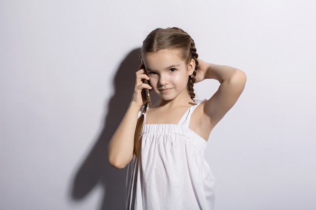 Happy little little girl caucasian talking on telephone over white background