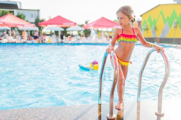 색색의 수영복을 입은 행복한 예쁜 소녀가 화창한 여름날 난간을 잡고 수영장을 떠납니다. 아이들을 위한 건강과 레크리에이션을 위한 따뜻한 나라의 휴가 개념