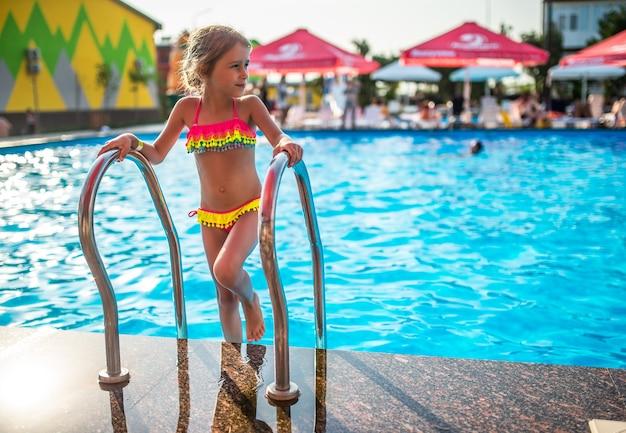 컬러 수영복에 행복하고 예쁜 소녀는 햇살 따뜻한 여름날에 난간을 잡고 수영장을 떠납니다. 어린이를위한 건강과 레크리에이션을위한 따뜻한 나라의 휴가 개념