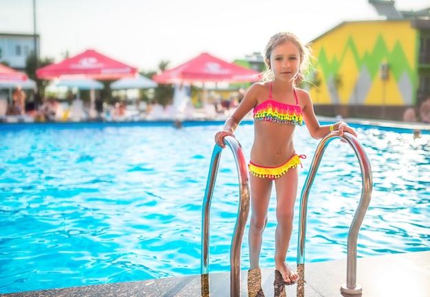 컬러 수영복에 행복 한 작은 예쁜 여자는 햇살 따뜻한 여름날에 난간을 잡고 수영장을 떠난다