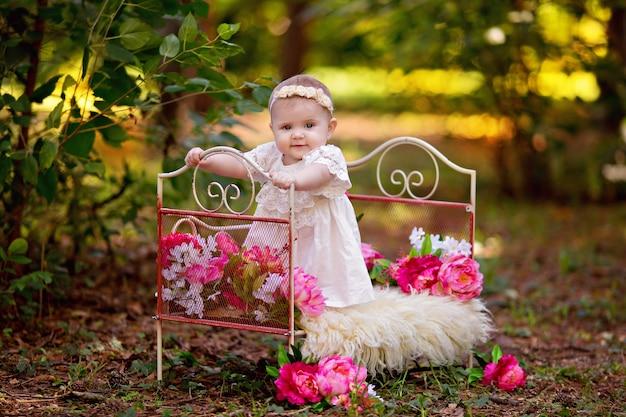 夏の屋外のピンクの花が付いているベッドで幸せな小さな王女の赤ちゃん