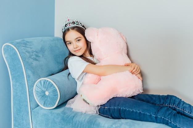 Счастливая маленькая принцесса играет с розовым медведем и короной на голове