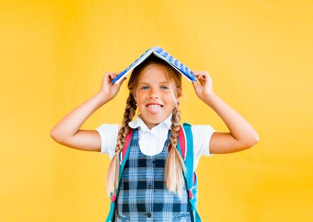 彼女の頭に本を持って、黄色の背景に立っている幸せな小さな女子高生。