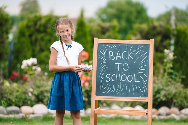 Happy little schoolgirl with a chalkboard outdoor