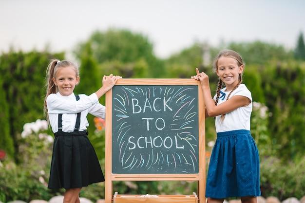 屋外の黒板で幸せな小さな女子学生