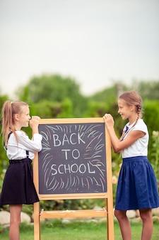 Happy little schoolgirls with a chalkboard outdoor