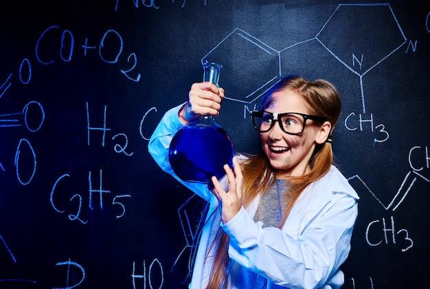 幸せな小さな科学者が実験をしている