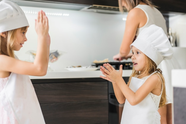 Happy little sisters in chef's hat playing in kitchen