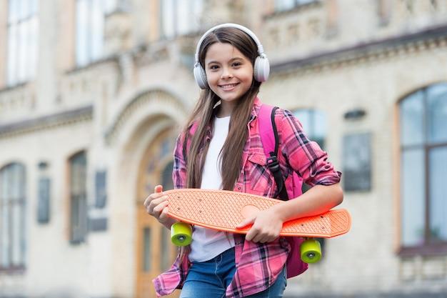 행복한 어린 스케이팅 소녀는 여름 도시 야외에서 헤드폰으로 음악을 들으며 스케이팅 보드를 들고 있습니다.