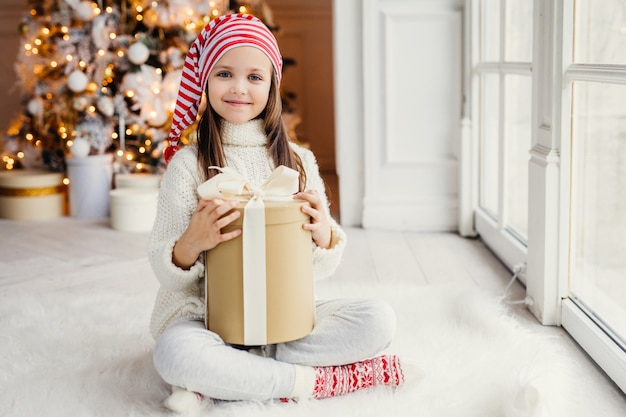 Happy little small child wears white knitted sweater holds gift sits in cozy room against new year tree, feels comfort, glad to recieve christmas present from parents. childhood, holidays concept