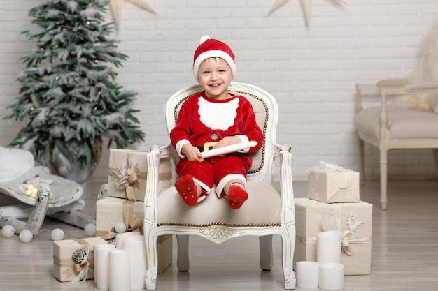 Happy little smiling boy in santa claus costume sits on armchair near christmas tree and holds white candle in hands