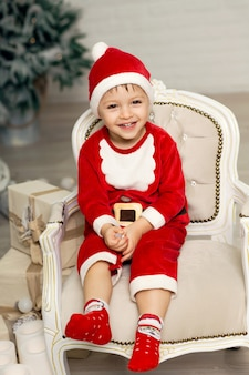 Happy little smiling boy in santa claus costume sits on armchair near christmas tree.