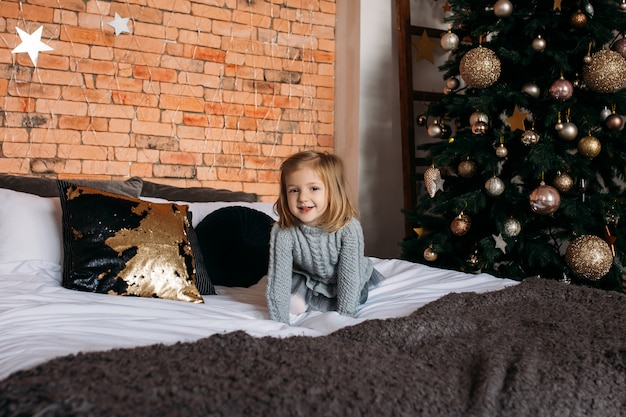 Happy little smiling girl on bed at home. christmas tree